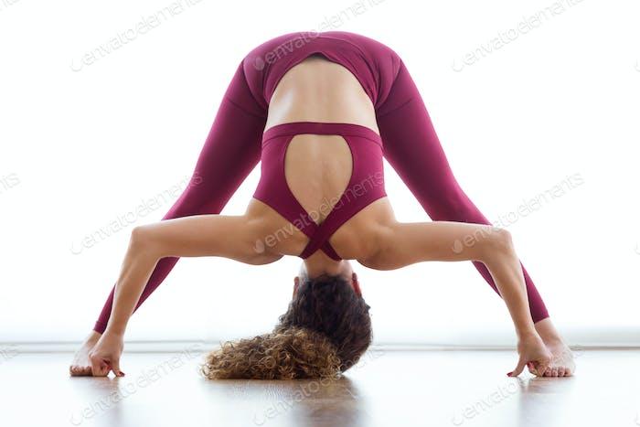 Hübsche junge Frau, die zu Hause Yoga praktiziert. Prasarita Paddotanas