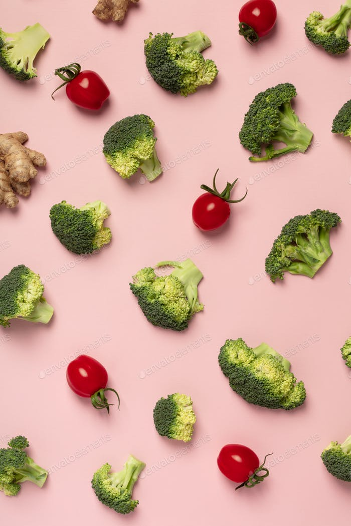 Colorful pattern of tomatoes, broccoli, ginger on a pink backgro