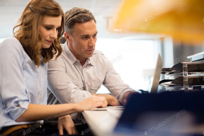 Business colleagues working together on laptop at desk