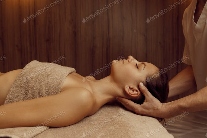 Male masseur rubbing neck vertebrae to young woman