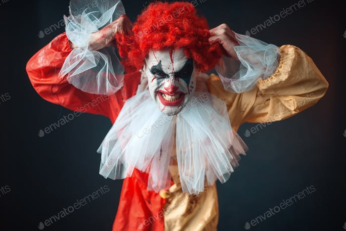 Scary bloody clown tears his hair, jerk in anger