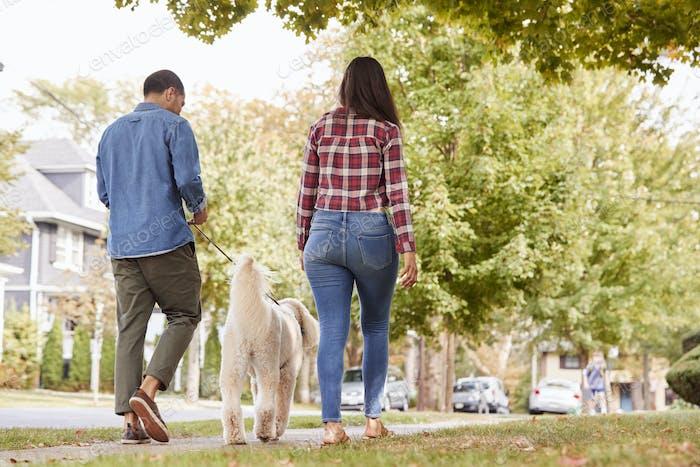 Rückansicht von Paar Walking Dog entlang Suburban Street