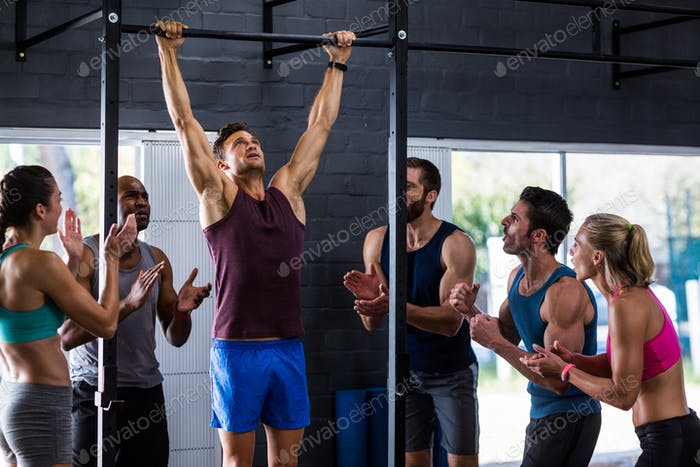 Friends cheering man doing chin-ups