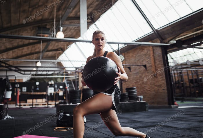 Fit woman exercising with a fitness ball at the gym