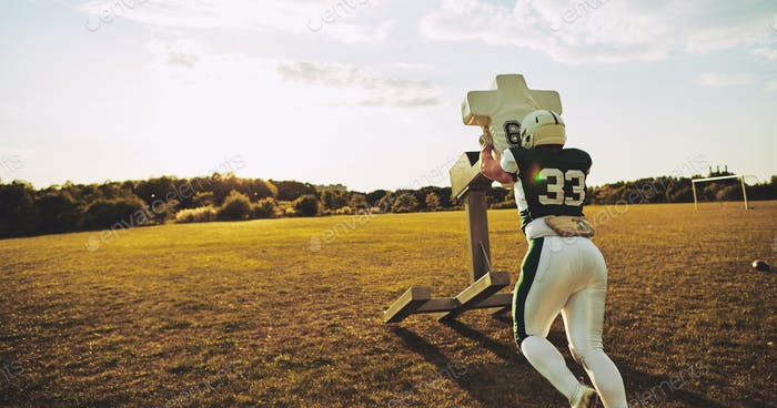 American football player doing tackling drills on a field