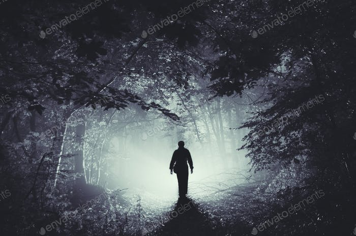 Silhouette of man in mysterious light in haunted woods