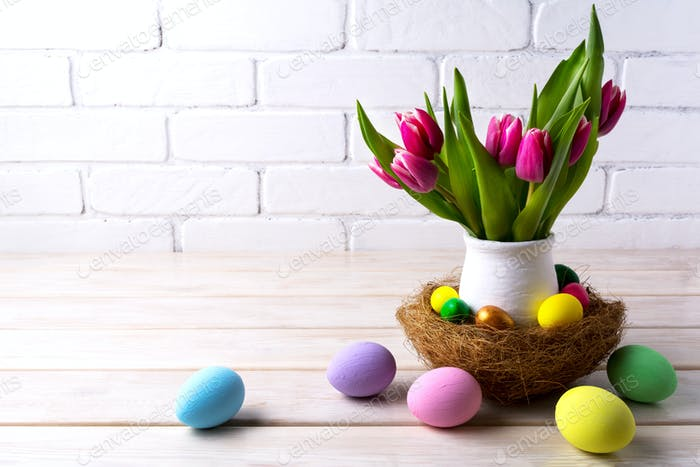 Easter table centerpiece with decorated eggs in nest