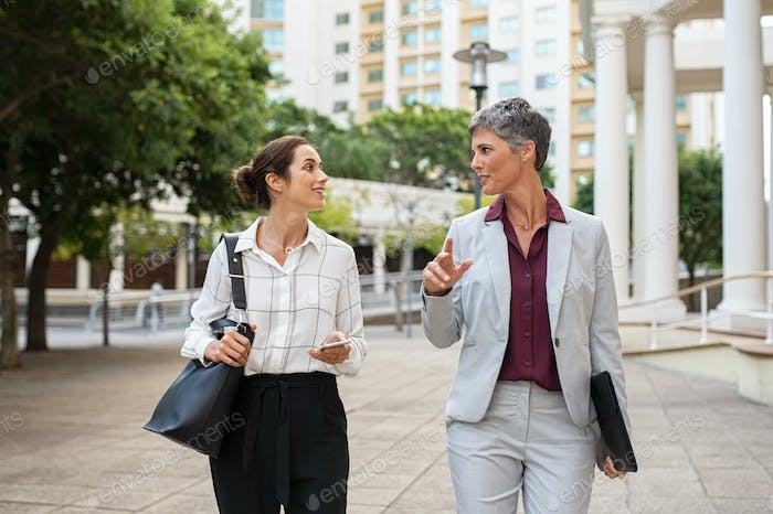 Mature business women in conversation while walking