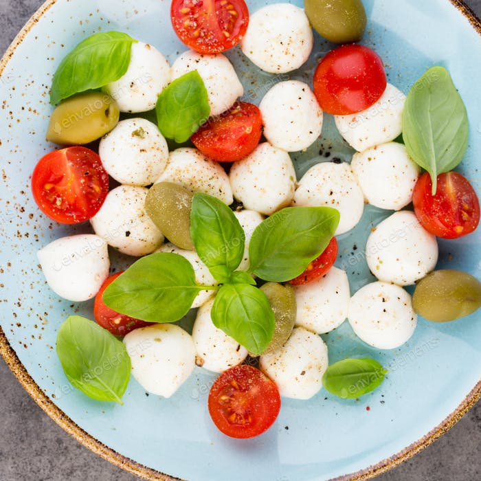 Cherry tomatoes, mozzarella cheese, basil and spices on gray slate stone chalkboard.