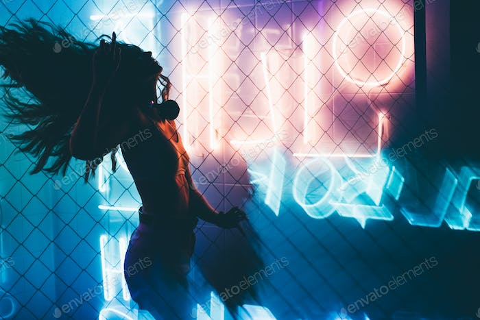 Dancing silhouette of girl in a nightclub.