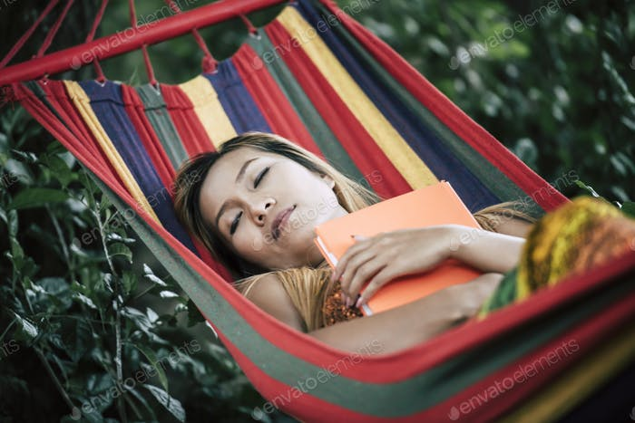 Young woman reading a book lying in a hammock