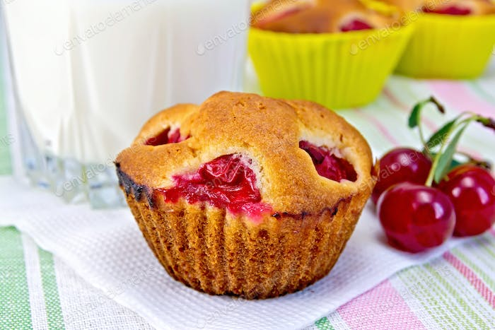 Cupcake with cherries and milk on napkin