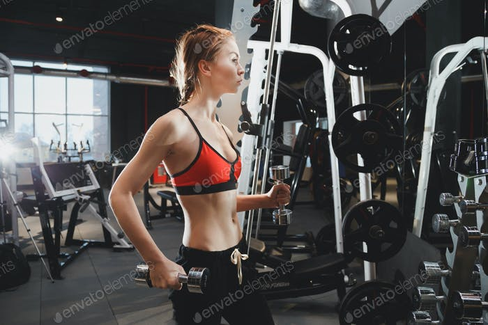 Young fitness woman with lifting dumbbells at gym