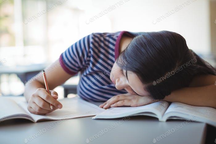 Tired schoolgirl sleeping in classroom