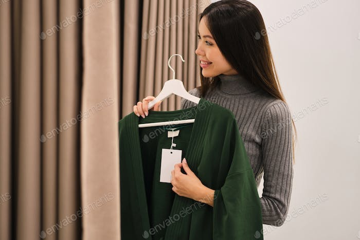 Side view of pretty smiling Asian girl joyfully trying on cardigan in fashion store