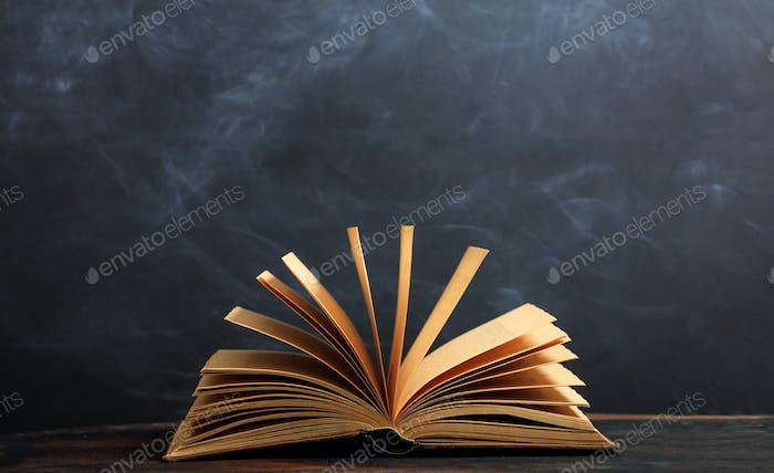 Vintage book on blackboard background