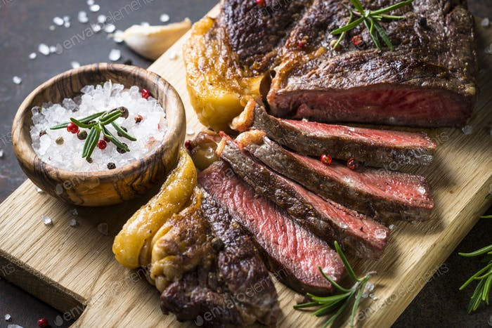 Grilled beef steak ribeye on wooden cutting board