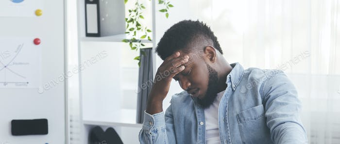 Overworked black businessman suffering from headache at workplace in office