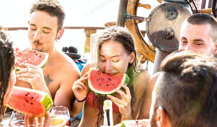 Glückliche Millenial-Freunde, die sich auf einer Segelbootparty mit Wassermelonen-Sangria amüsieren