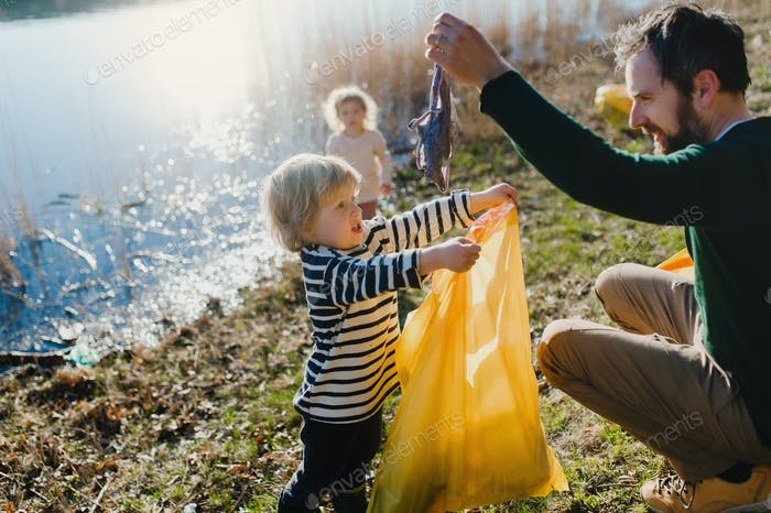 Father with small kids collecting rubbish outdoors in nature, plogging concept