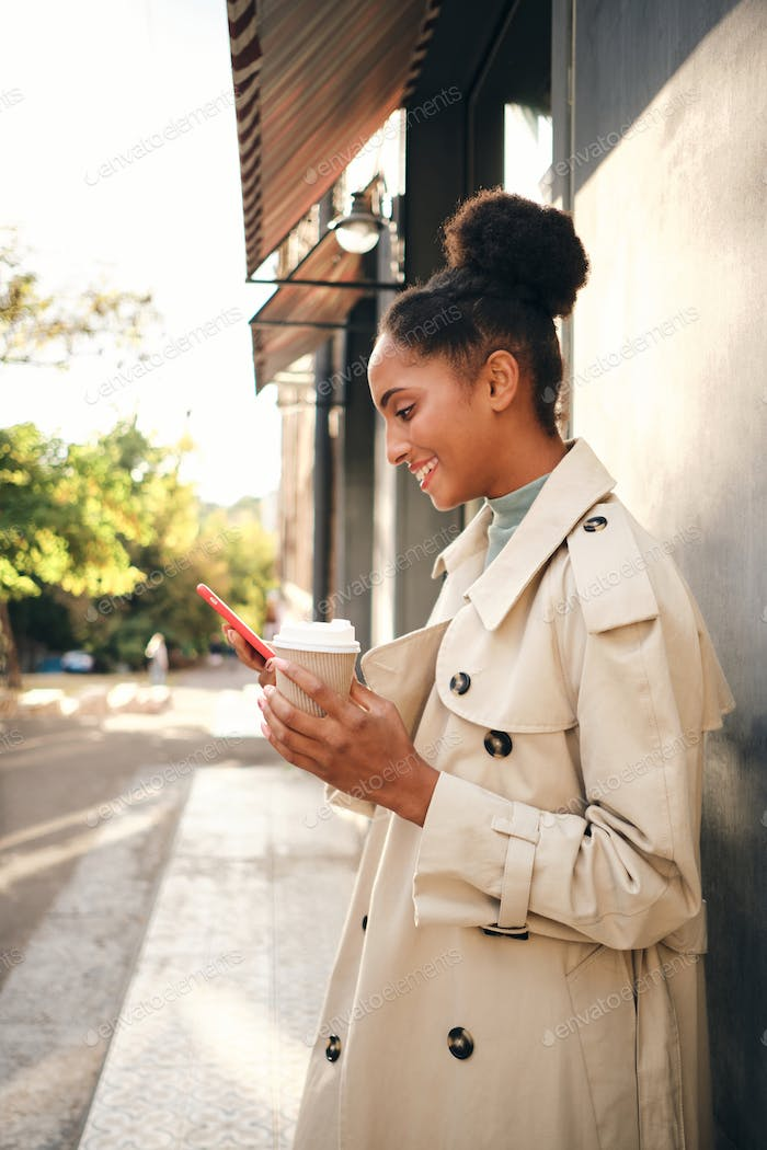 Smiling African American girl in stylish trench coat with coffee joyfully using cellphone outdoor