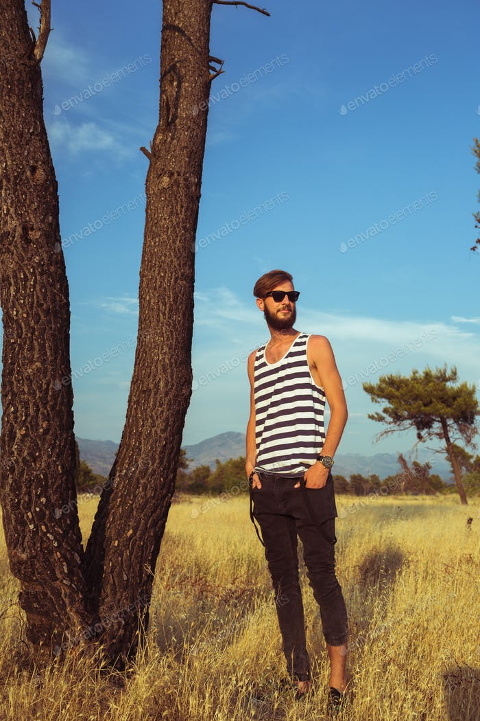 Young stylish handsome man in the savannah