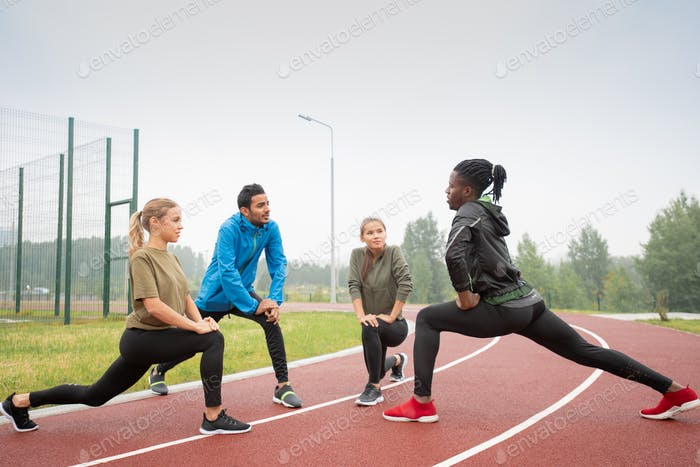 Four young friendly active people in sportswear exercising on racetracks