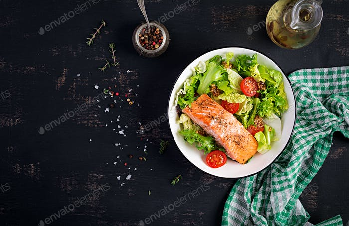 Baked salmon fillet with fresh vegetables salad. Top view, overhead