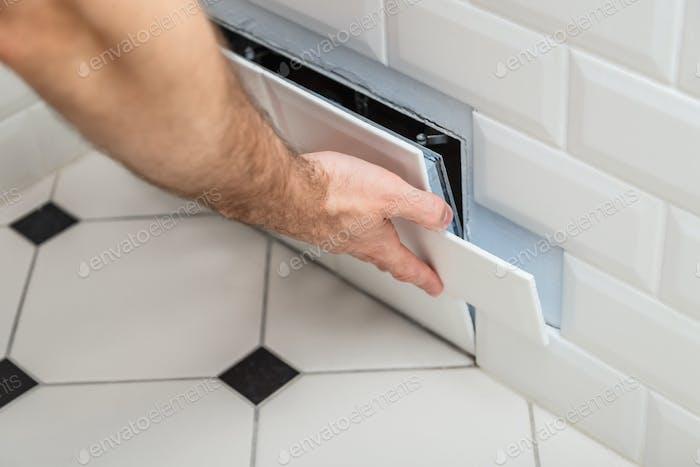 Öffnen Sie versteckte Revision Sanitärluke an der Wand der Fliesen unter dem Badezimmer