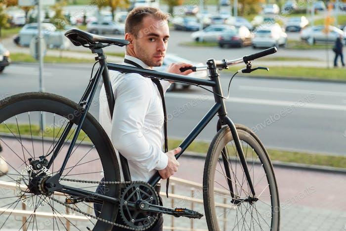 Hübscher junger Geschäftsmann in einem weißen Hemd und schwarze Krawatte trägt sein Fahrrad