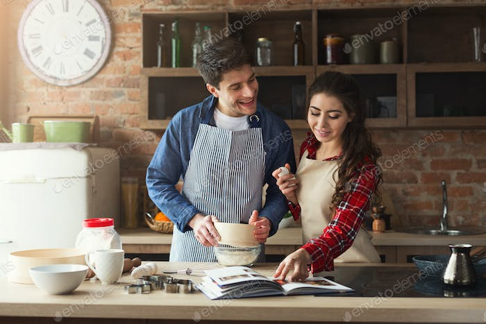 Happy young woman and man baking in loft kitchen