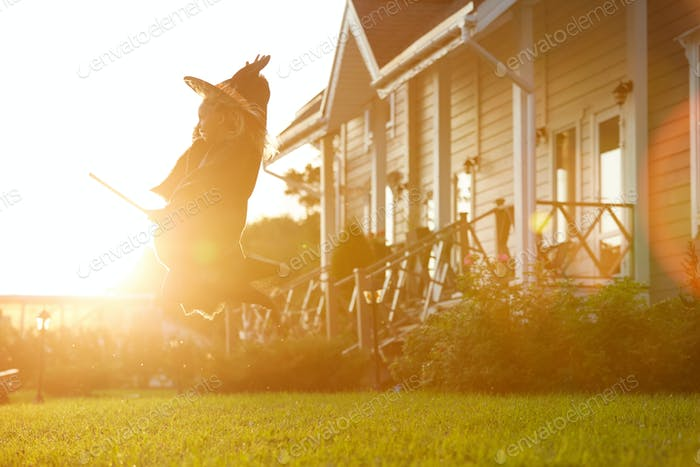 Cute Witch Flying on Broom in Sunlight