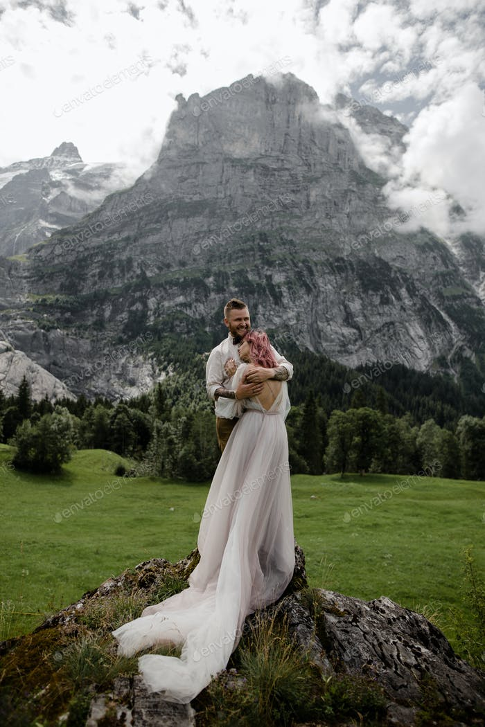 Happy Young Wedding Couple Hugging While Standing on Rock in Alpine Valley