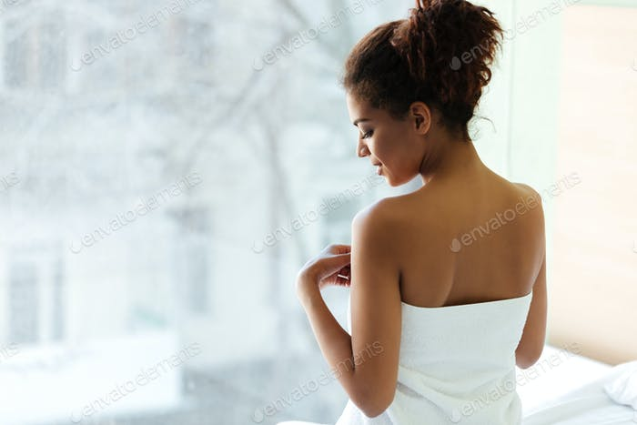Amazing young african woman dressed in towel near window