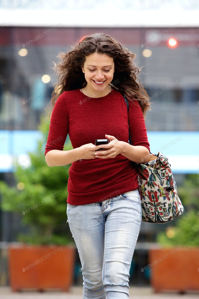 Happy young urban woman walking with mobile phone