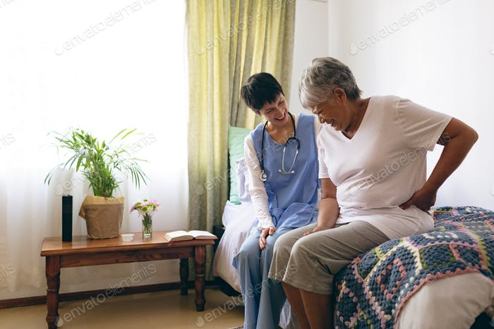 Female doctor and senior female patient interacting with each other at retirement home