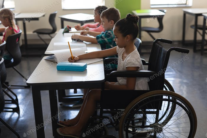 Disabled schoolgirl studying in classroom
