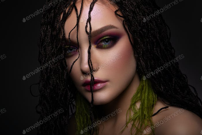 Woman with colorful make up and braids