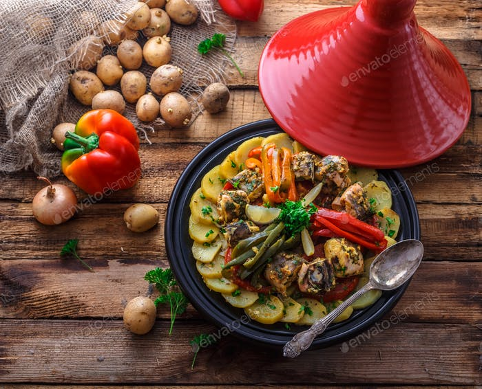 Fish tajine mqualli with potato and bell peppers, top view