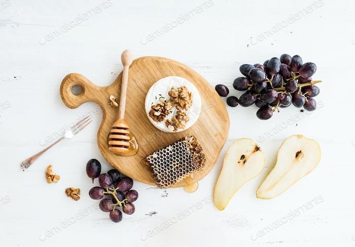 Camembert-Käse mit Trauben, Walnüssen, Birne und Honig auf Eichen-Servierbrett