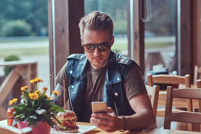 Handsome hipster with a stylish haircut and beard sits at a table in a roadside cafe