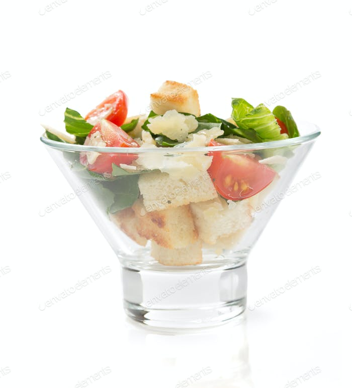 caesar salad in glass bowl on white background