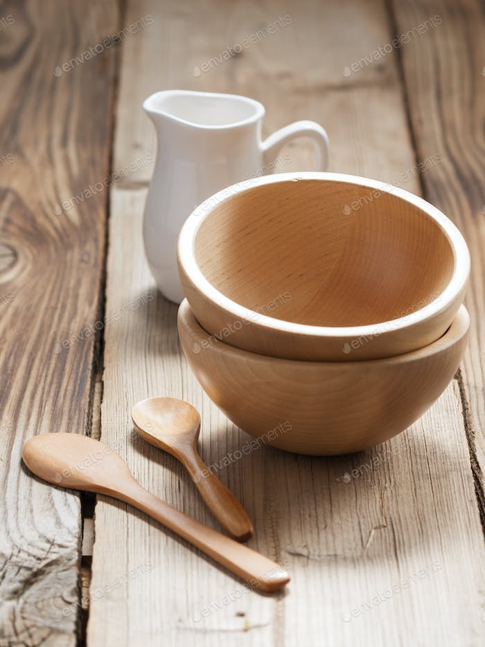 Wooden bowls and a small jug on the wooden background