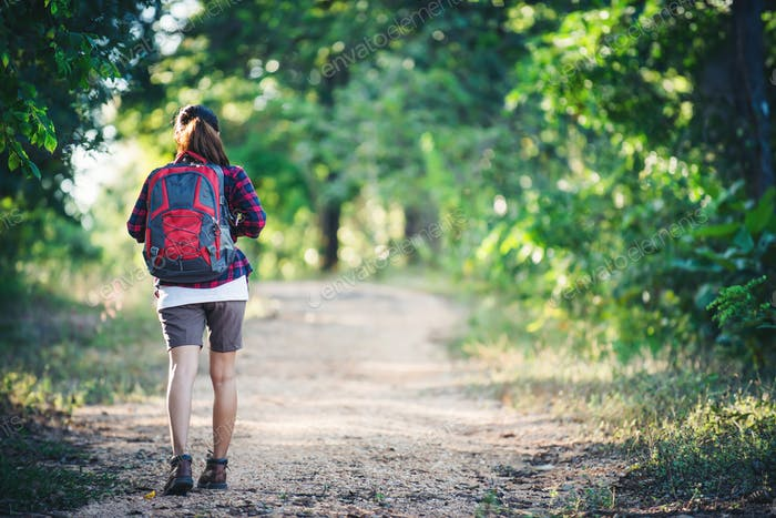 Rear of young woman hiker with backpack walking on a country trail.