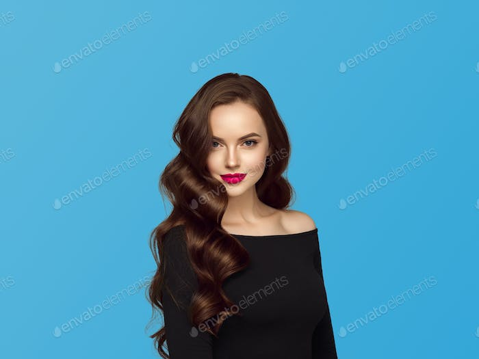 Beautiful hair woman with long brunette hair beauty healthy hairstyle. Blue background.