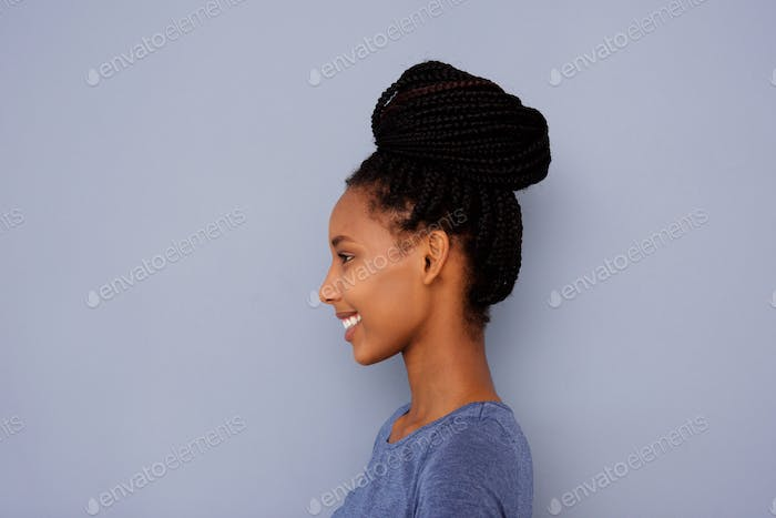 young girl with braided hair in a bun by gray wall