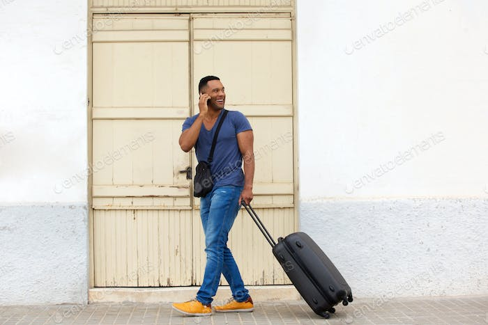 Full body handsome young guy walking with suitcase and talking on mobile phone