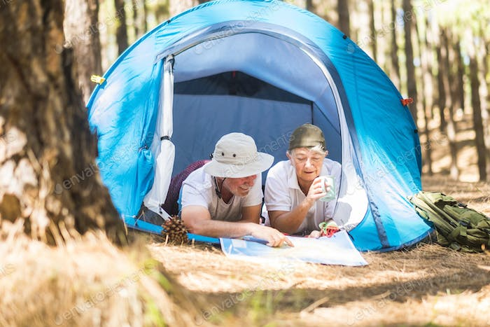 Caucasian traveler adult couple lay down inside a tent while choose and plan on a map