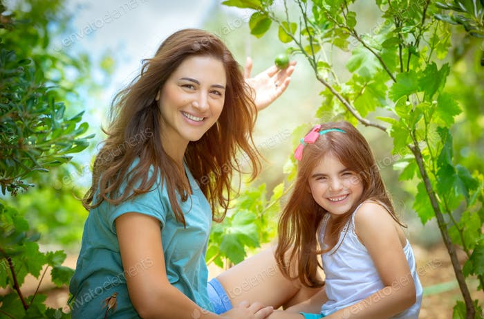 Mother with daughter in the orchard