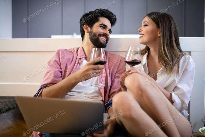 Happy smiling couple using laptop at home